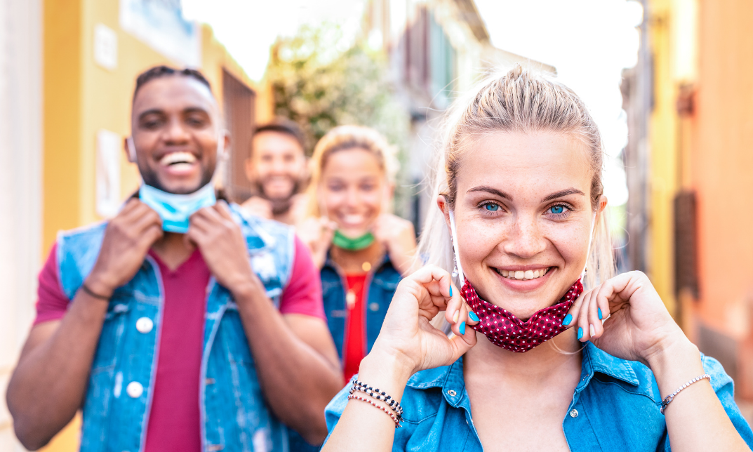 Young people smiling while pulling down their face masks outside